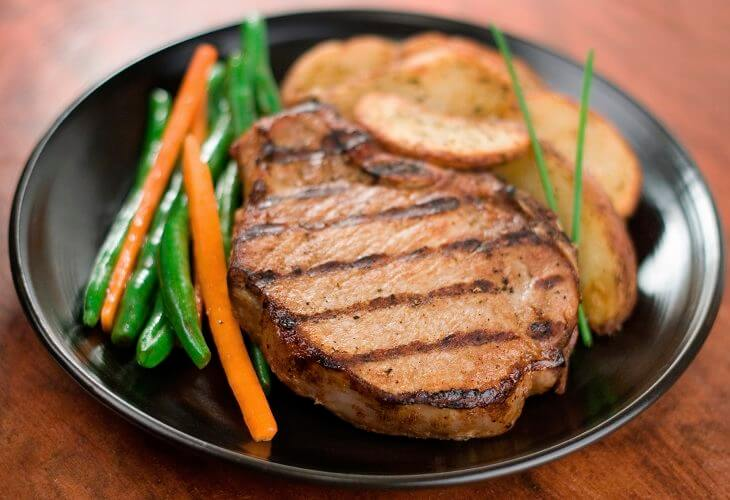 Delicious seasoned grilled pork chop dinner with glazed green beans and carrots and roasted herbed potatoes.  Shallow dof.